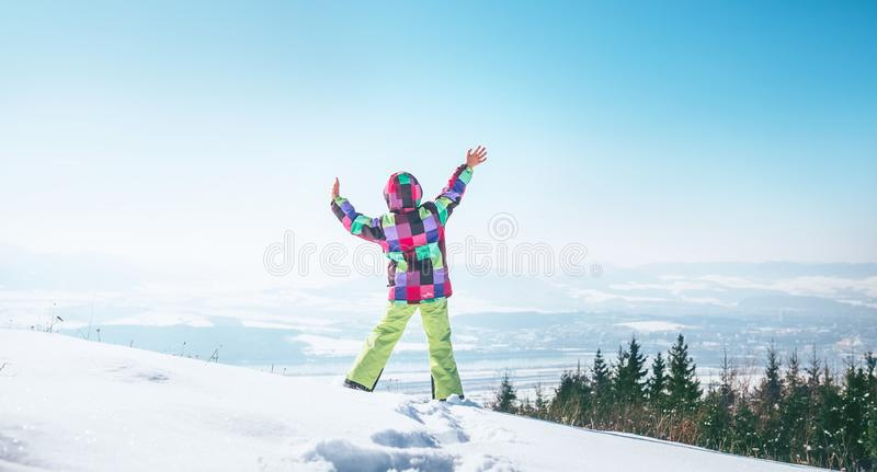Happy little girl jumping on the snow hill stock images