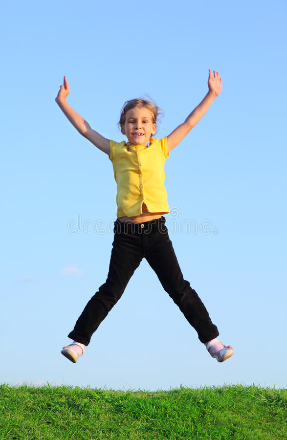 Happy little girl jumps at grass royalty free stock photos