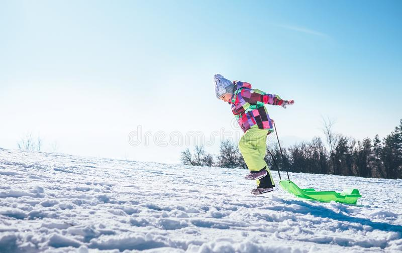 Happy little girl jumps up on the snow slope with bright plastic stock photography