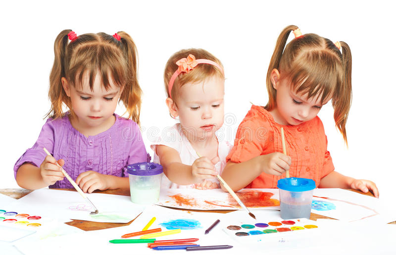 Happy little girl in kindergarten draw paints on white background royalty free stock image