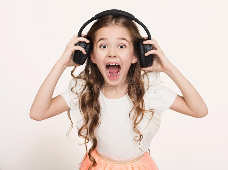 Happy little girl listen to music in headphones, white background royalty free stock images