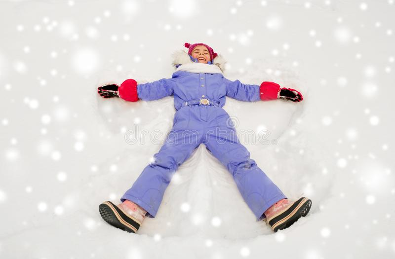 Happy little girl making snow angels in winter royalty free stock photo