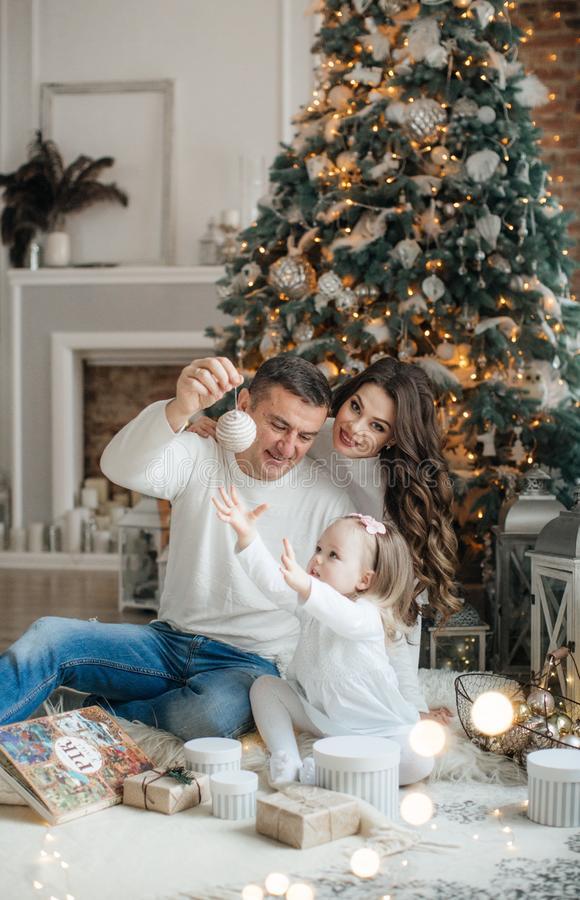 Happy little girl with mom and dad among the New Year`s scenery stock photography