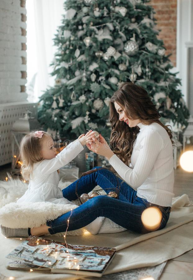 Happy little girl with mom among the New Year`s scenery stock photography