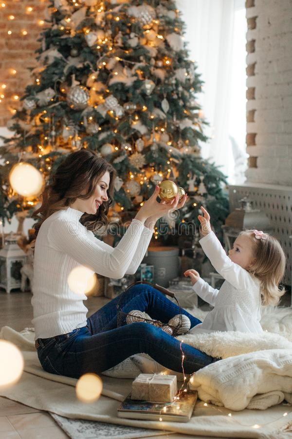 Happy little girl with mom among the New Year`s scenery royalty free stock image