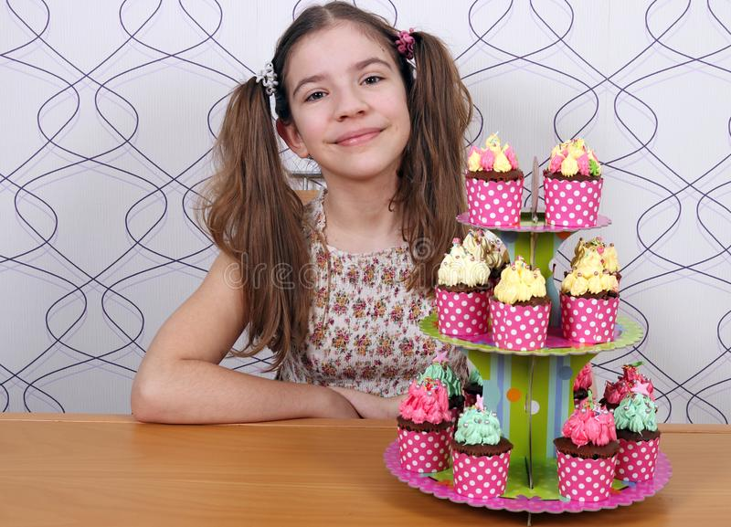 Happy little girl with muffins stock photography