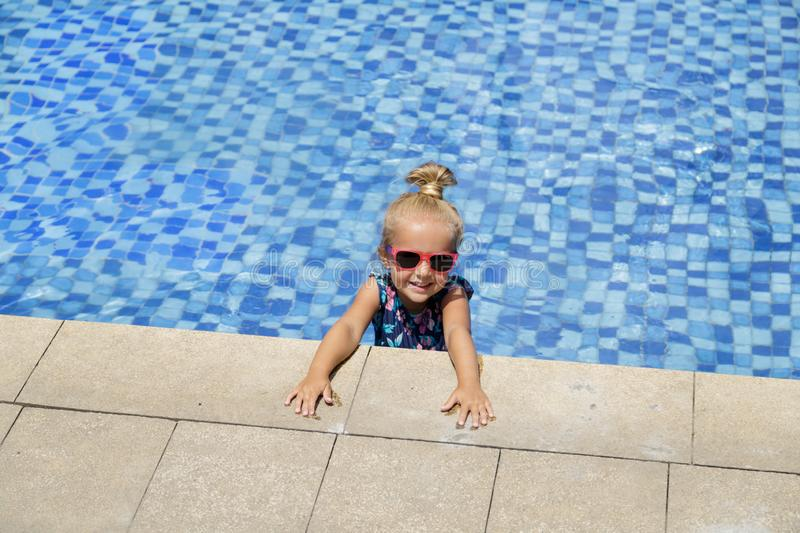 Happy little girl in outdoor swimming pool on hot summer day. Kids learn to swim. Children play in tropical resort. Family beach stock photos
