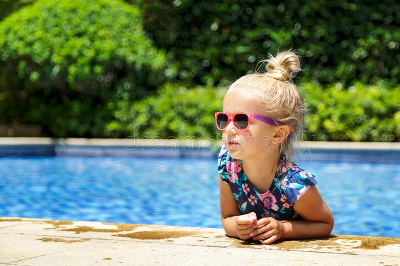 Happy little girl in outdoor swimming pool on hot summer day. Kids learn to swim. Children play in tropical resort. Family beach stock photo