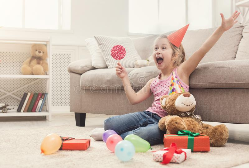 Happy girl celebrating birthday at home. Happy little girl in party hat celebrating birthday. Smiling kid sitting on floor among gifts and balloons, holding stock photos