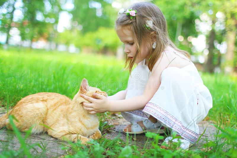 Happy little girl pets the cat in summer outdoors. Happy little 3 years girl pets the cat in summer outdoors stock photo