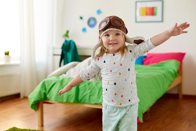 Happy little girl in pilot hat playing at home. Childhood, imagination and dream concept - happy little girl in pilot hat playing game at home stock image