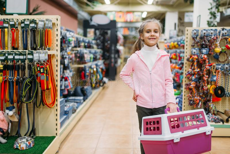 Happy little girl with carrier for cat in pet shop royalty free stock photography