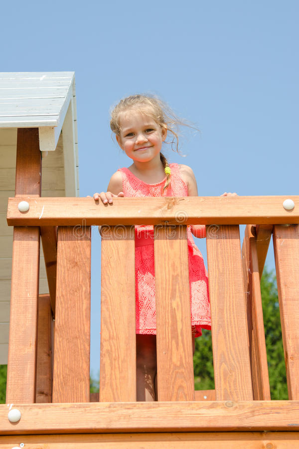 Happy little girl in pink dress on playground royalty free stock photography