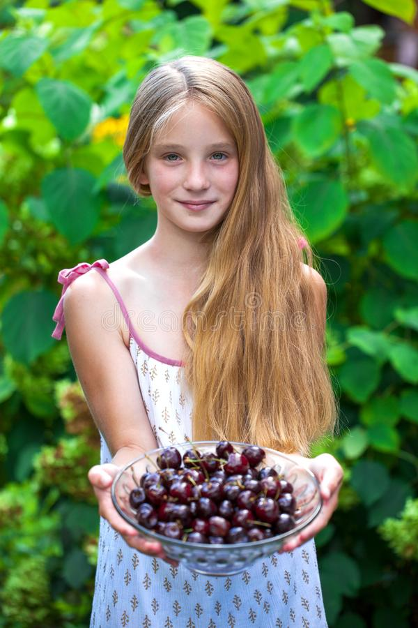 Happy little girl with a plate of sweet cherry royalty free stock images