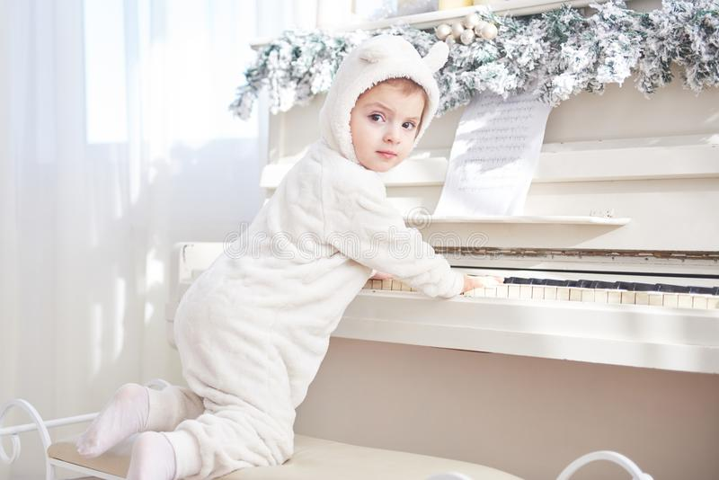 Happy little girl play the piano on Christmas day stock photo