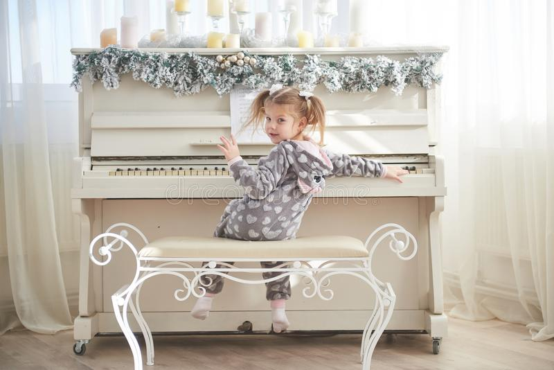 Happy little girl play the piano on Christmas day stock image