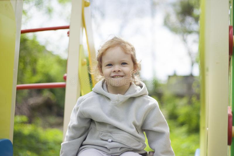 A happy little girl on the playground climbed onto a children slide and began to laugh and giggle stock photo