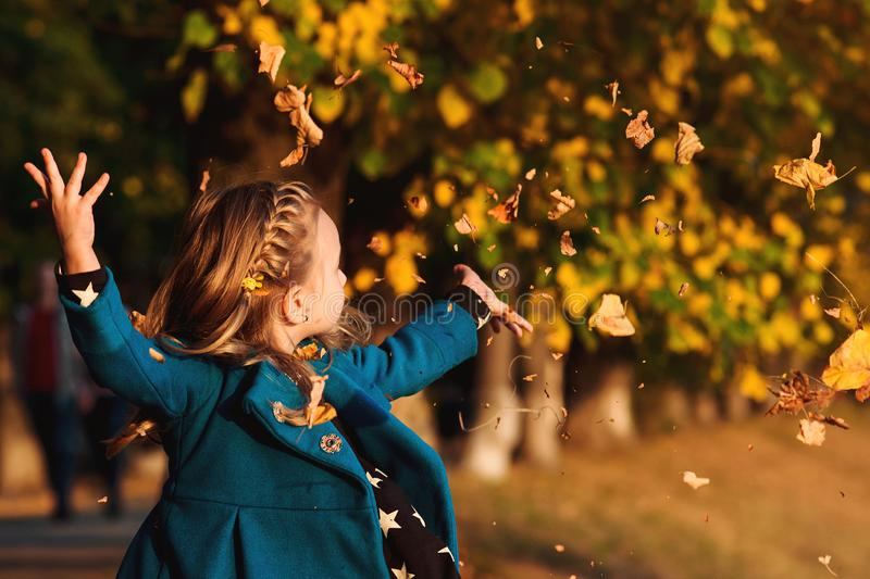 Happy little girl playing with autumn leaves. Cute child having fun in park. Stylish baby girl in blue coat throws autumn leaves o stock photos
