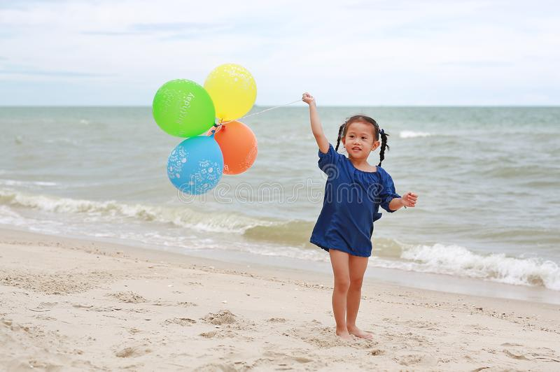 Happy little girl playing colorful balloons on the beach during summer vacation royalty free stock photography
