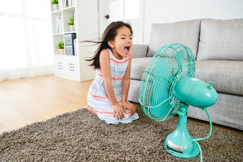 Happy little girl playing electric fan at home royalty free stock images