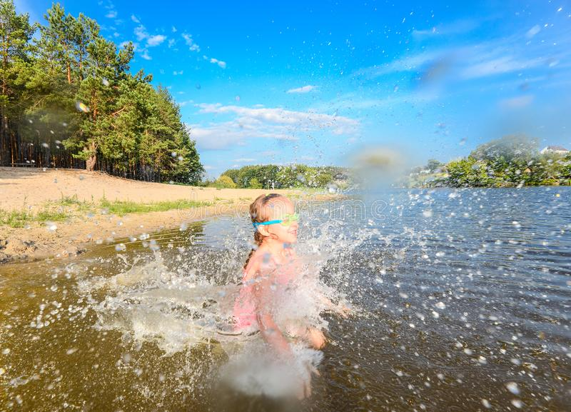 Happy little girl playing in the lake on the sandy beach near forest. stock image