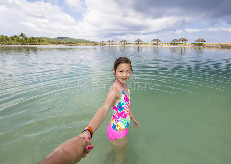 Happy little girl playing in the ocean on a family vacation stock images
