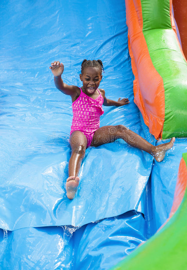 Happy little girl playing outdoors on an inflatable bounce house water slide. Cute little African American girl playing on an inflatable bounce house outdoors royalty free stock image