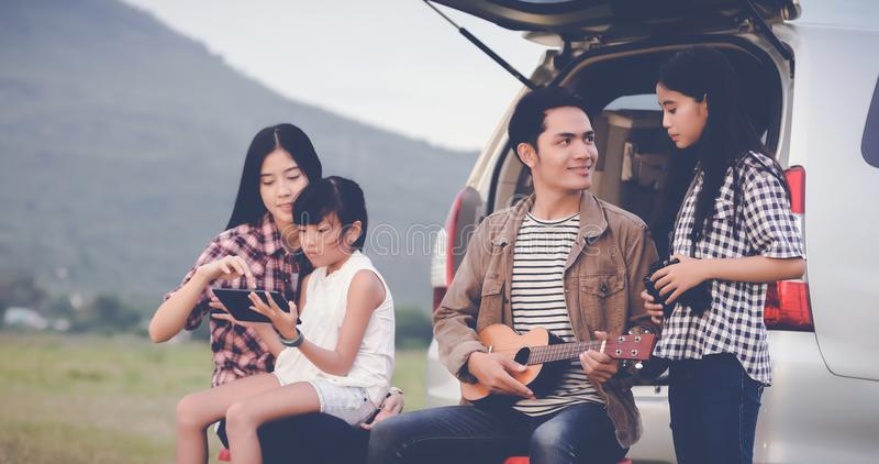 Happy little girl playing ukulele with asian family sitting in t. He car for enjoying road trip and summer vacation,soft focus royalty free stock images