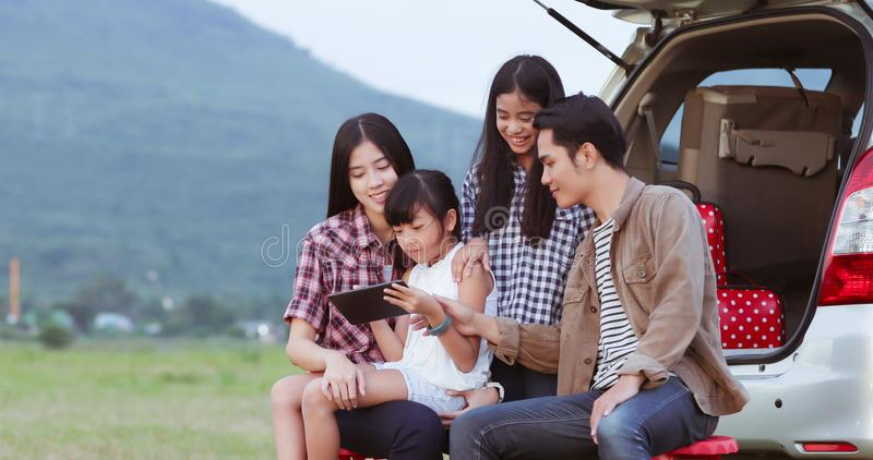 Happy little girl playing ukulele with asian family sitting in t. He car for enjoying road trip and summer vacation,soft focus royalty free stock photography