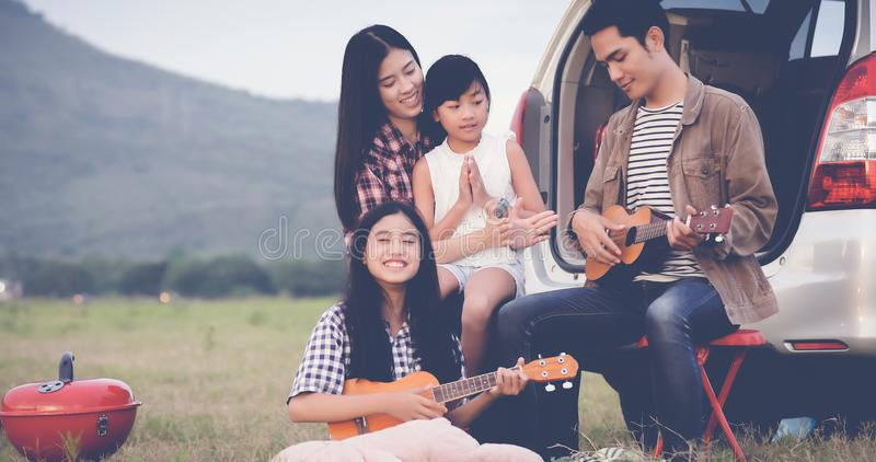 Happy little girl playing ukulele with asian family sitting in t. He car for enjoying road trip and summer vacation,soft focus royalty free stock image