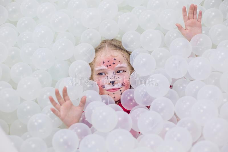 Happy little girl in a playroom in a white room stock image