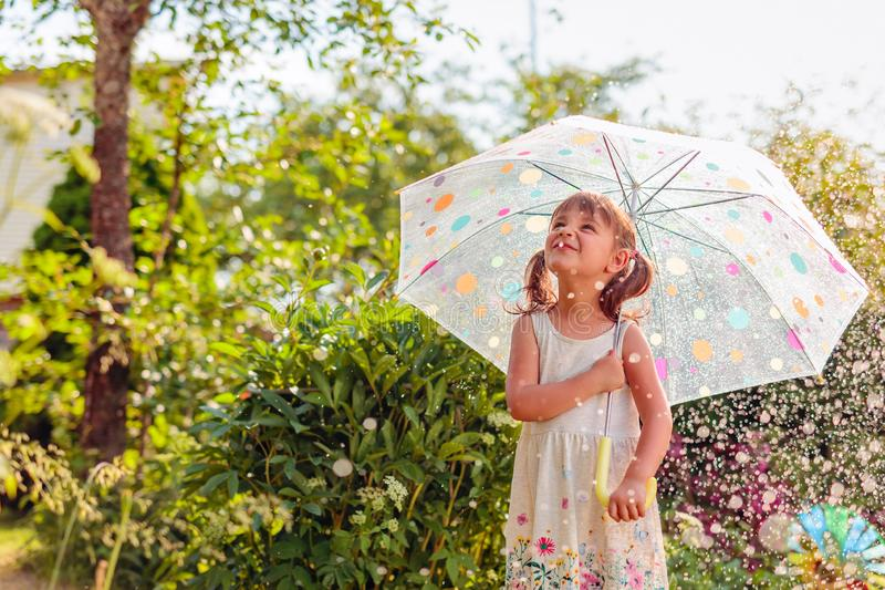 Happy little girl in garden under the summer rain with an umbrella. Happy little girl plays in garden under the summer rain with an umbrella. Expressive facial royalty free stock photos
