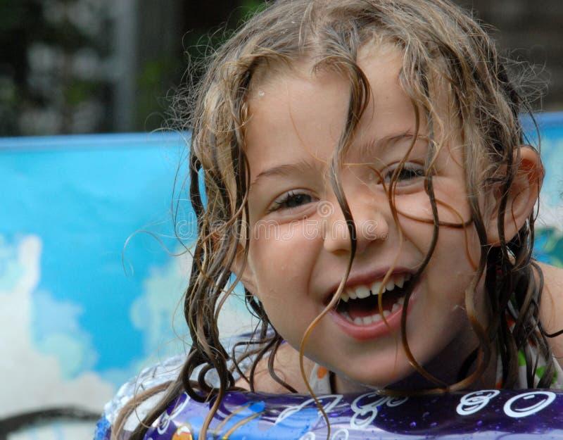 Happy little girl in pool stock image