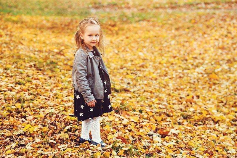 Happy little girl portrait outdoors. Autumn time. Little blondy girl in stylish leather coat and dress at autumn park. Happy royalty free stock photography