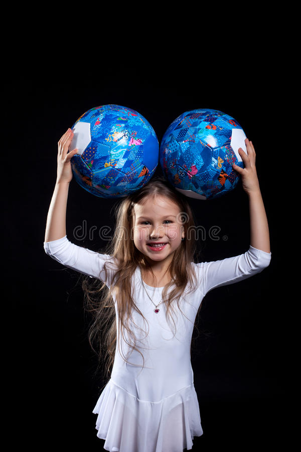 Happy little girl posing with gymnastic balls royalty free stock photos