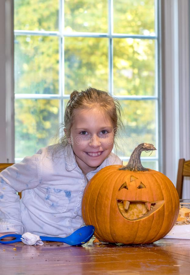 A happy little girl and her Halloween pumpkin. A happy little girl proudly shows off her Halloween pumpkin creation royalty free stock photography