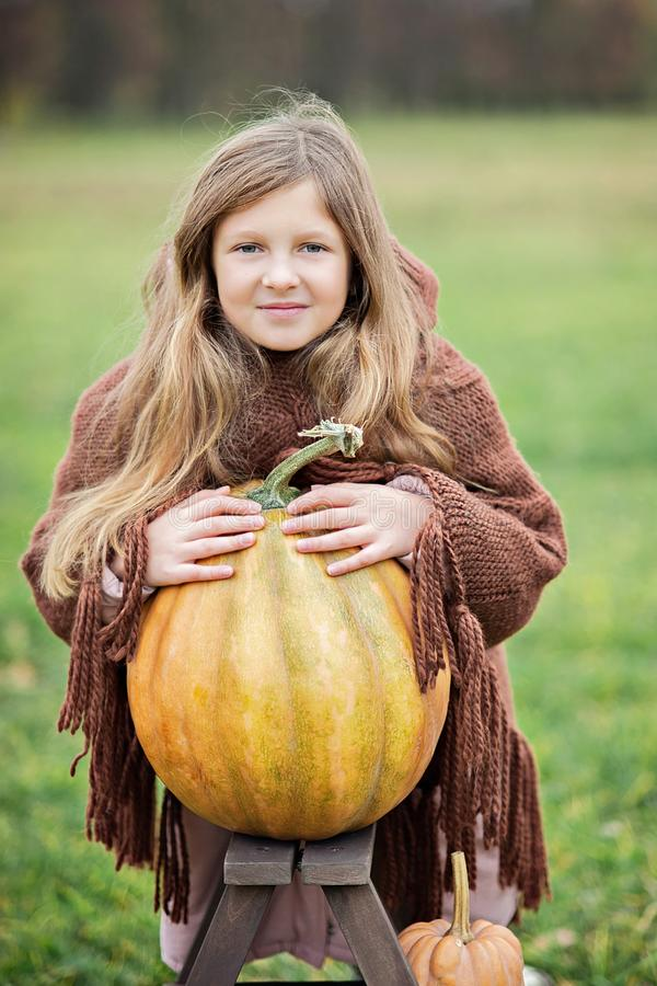 Happy little girl on pumpkin patch on cold autumn day, with a lot of pumpkins for halloween or thanksgiving royalty free stock image