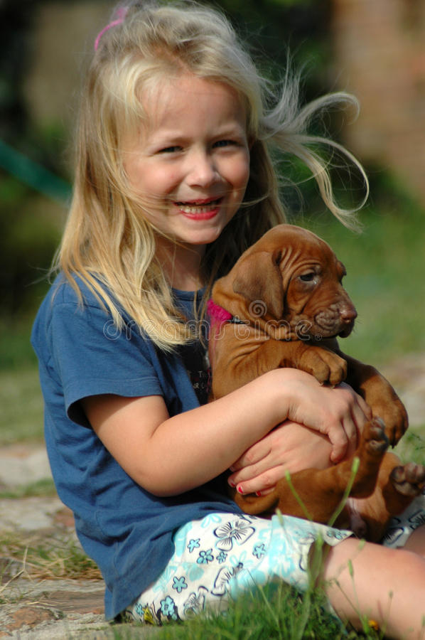 Happy little girl with puppy. A beautiful Caucasian girl child with happy smiling facial expression hugging and singing for her Rhodesian Ridgeback hound dog royalty free stock images