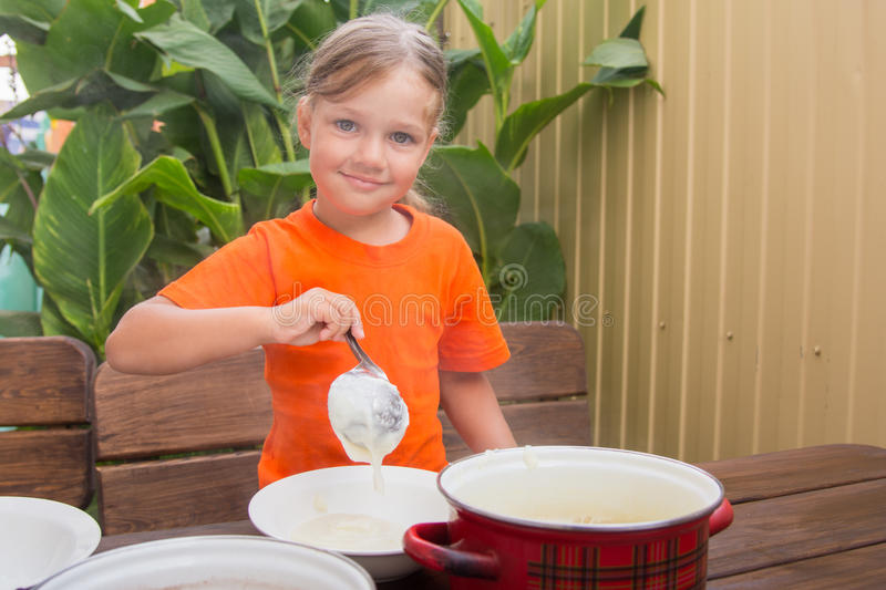 Happy little girl puts cereal in a bowl stock images