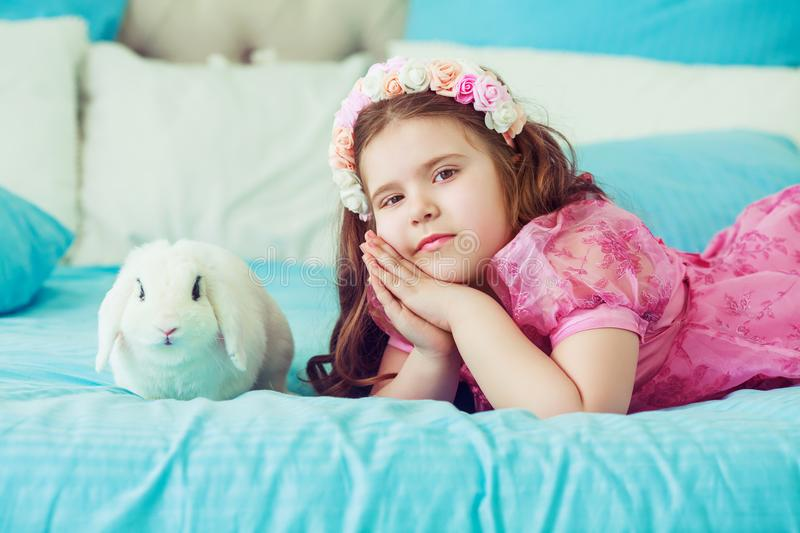 Happy little girl with a rabbit stock photos