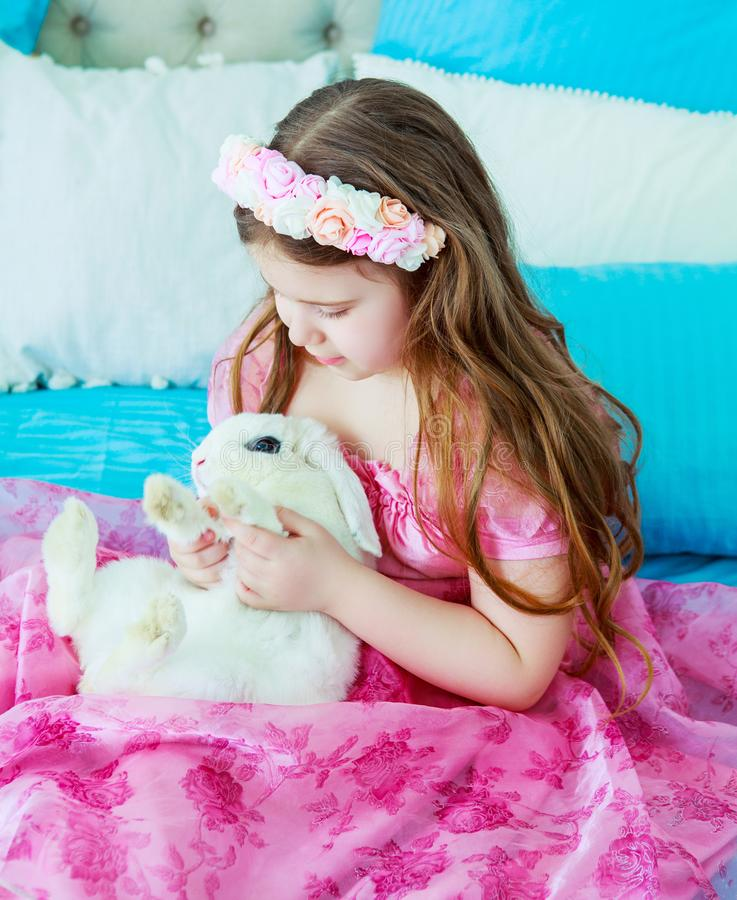 Happy little girl with a rabbit stock images