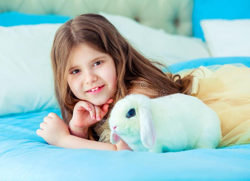Happy little girl with a rabbit royalty free stock photos