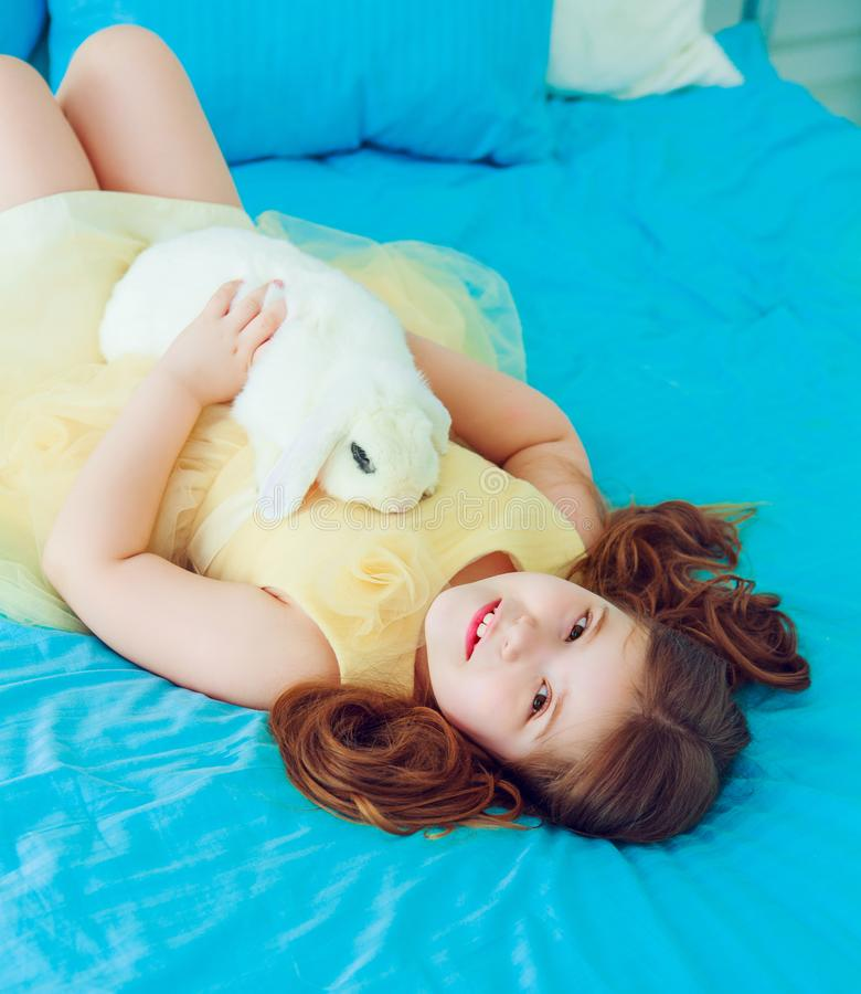 Happy little girl with a rabbit royalty free stock image
