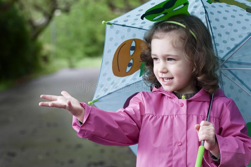 A happy little girl in a rainy day. A happy little girl, with a colorful umbrella and a pink raincoat, tries to catch the rain with her hand stock photography