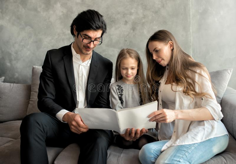 Happy little girl reads a book with her parents royalty free stock photography