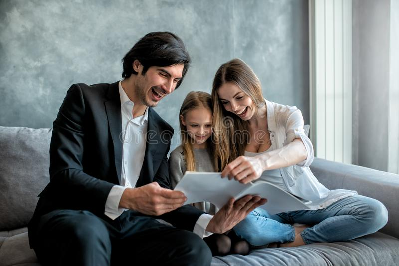 Happy little girl reads a book with her parents royalty free stock image