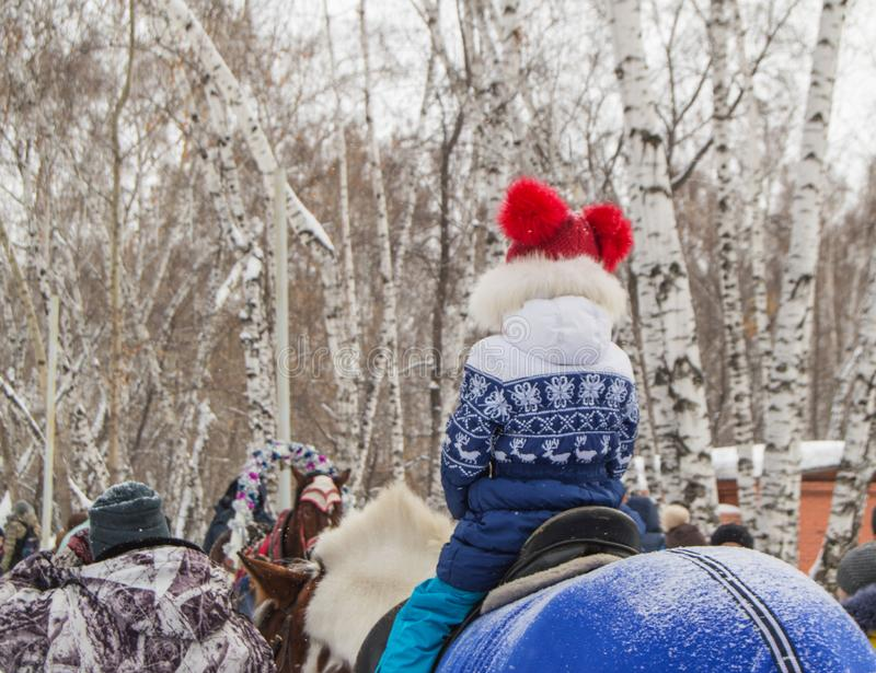 Happy little girl in a red hat with pompoms and a blue jacket with deer riding a pony in a winter Park, the pleasure of royalty free stock photography