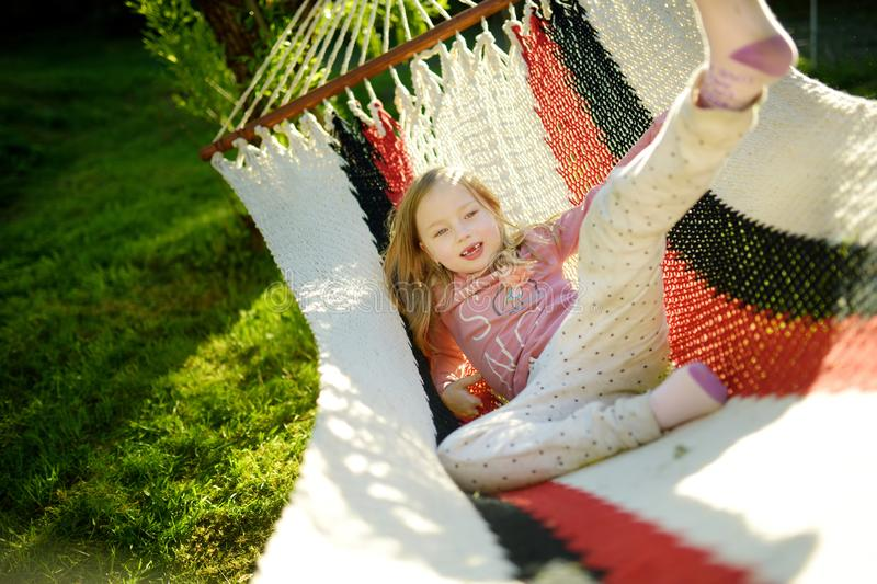 Happy little girl relaxing in hammock on beautiful summer day. Cute child having fun in spring garden. royalty free stock photography