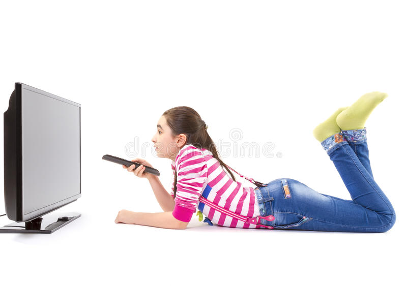 Happy little girl with remote control watching tv stock image