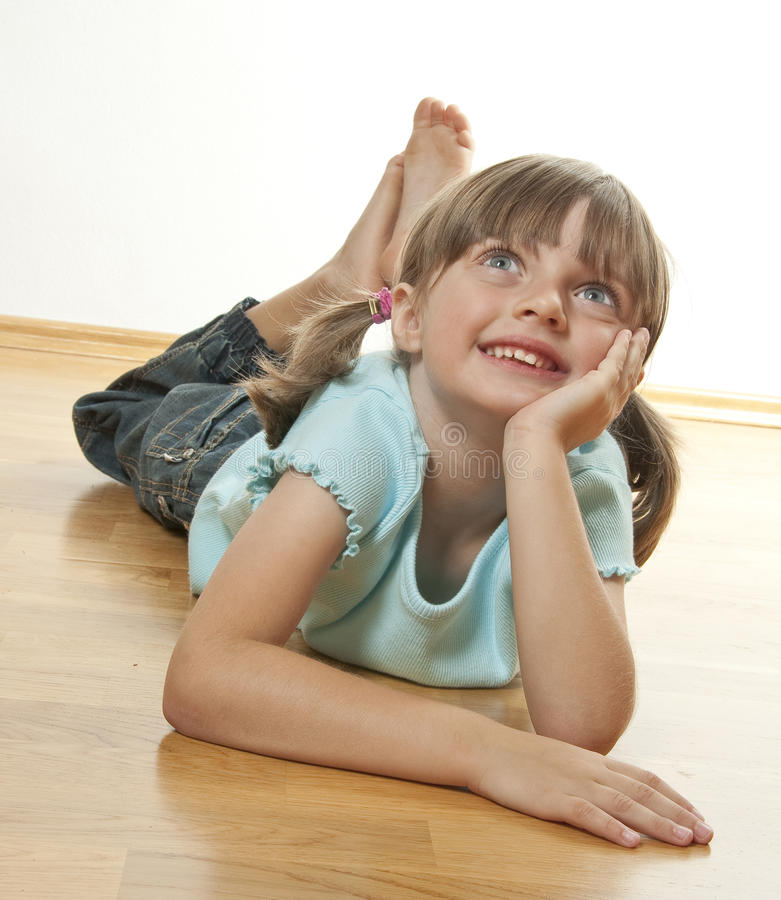 Happy little girl resting on a wooden floor stock photography